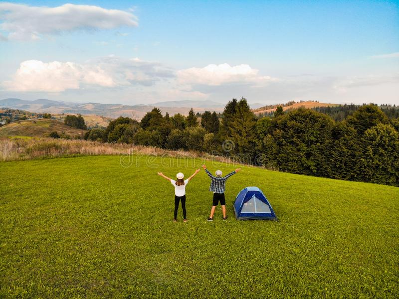 Aerial view of hiker couple raised hands up to sunlight on green grass in mountain near camping. stock image