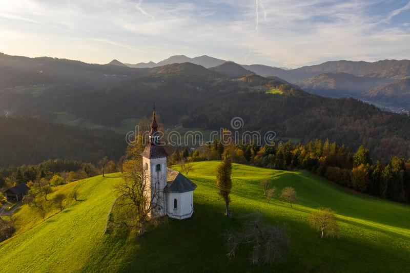 Aerial view of hills, colorful forest and Sv Tomaz church. Sunset in Slovenia in autumn.  royalty free stock image