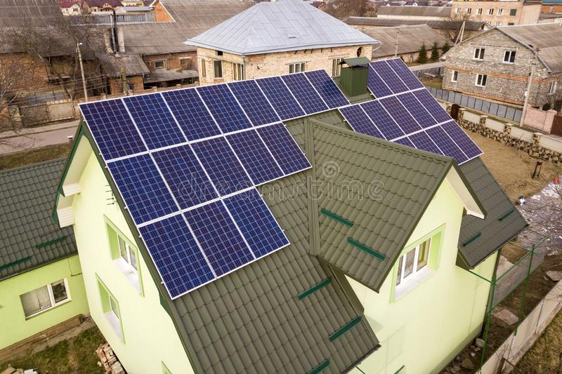 Aerial view of  house cottage with blue shiny solar photo voltaic panels system on the roof. Renewable ecological green energy. Production concept stock image