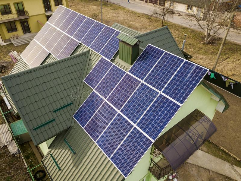 Aerial view of  house cottage with blue shiny solar photo voltaic panels system on the roof. Renewable ecological green energy. Production concept stock photo