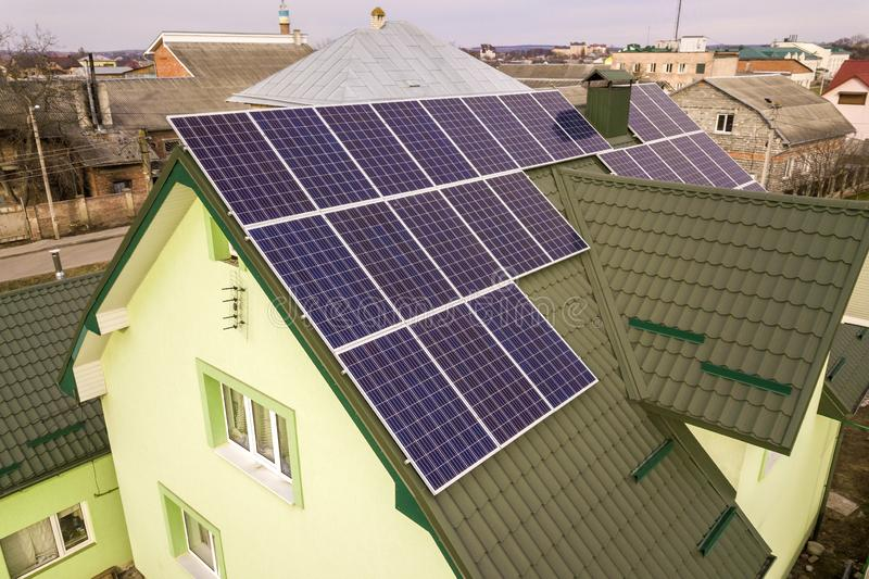 Aerial view of  house cottage with blue shiny solar photo voltaic panels system on the roof. Renewable ecological green energy. Production concept royalty free stock image