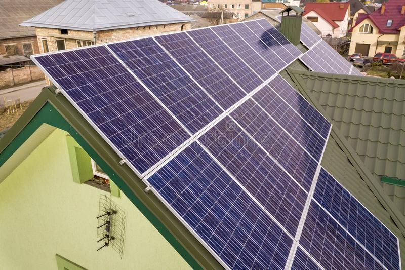 Aerial view of  house cottage with blue shiny solar photo voltaic panels system on the roof. Renewable ecological green energy. Production concept stock photos