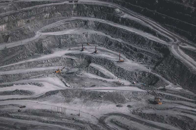 Aerial view industrial of opencast mining quarry with lots of machinery at work - view from above. Extraction of lime, chalk, calx, caol stock photography