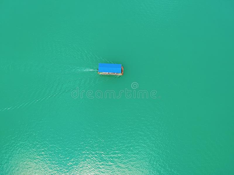 Aerial view of Jablanicko lake in Bosnia and Herzegovina near village Ostrozace with small boat with blue roof. Sailing on turquoise water stock images