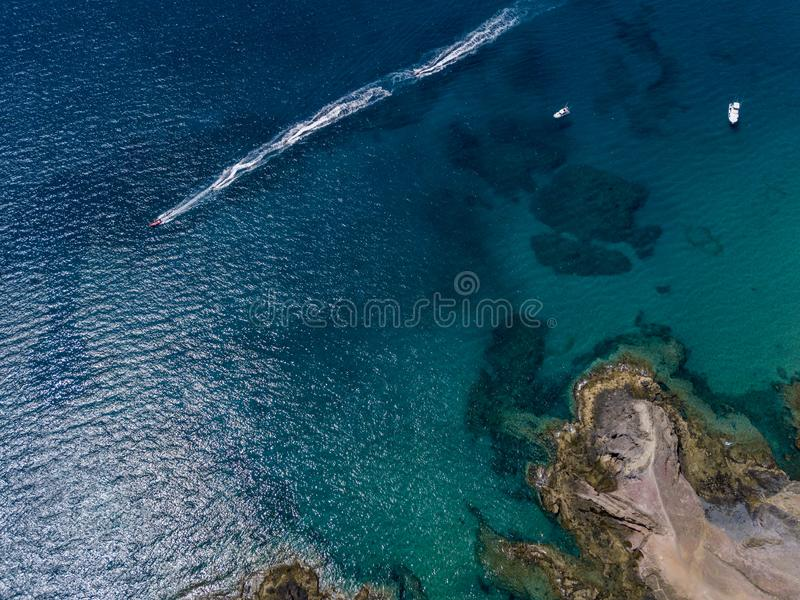 Aerial view of the jagged shores and beaches of Lanzarote, Spain, Canary. Red dinghy navigates followed by watercraft. Aerial view of the jagged shores and stock photos