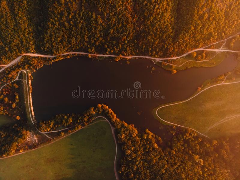 Aerial view of lake, forest and warm sunset or sunrise. Top view royalty free stock images