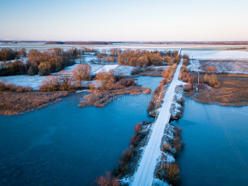 Aerial view of lake and snow covered bridge over it during nice sunrise in Lithuania - Winter landscape stock images