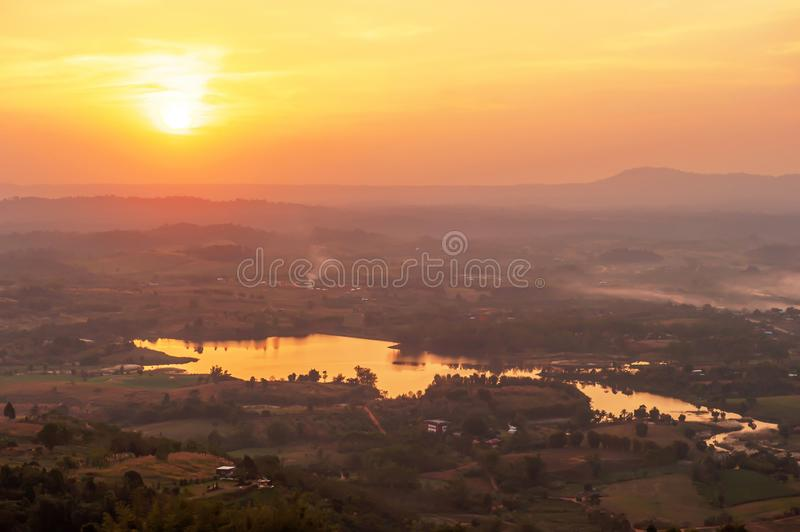 Aerial view of lake with the sun setting over a mountain range royalty free stock image