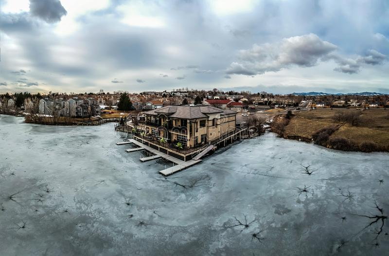 Aerial view of a lakefront restaurant in Denver Colorado. Aerial view from above frozen lake looking at a lake front restaurant with boat docks. Awesome clouds stock photos