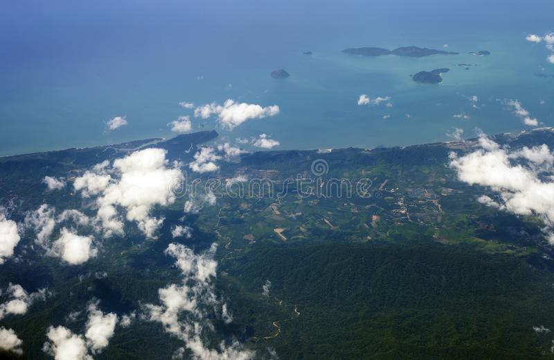 Aerial view of land and blue sea, Thailand. Aerial view of land and blue sea from airplane window. Thailand landscape, top view royalty free stock photo