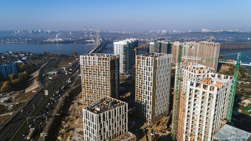 Aerial view of landscape in the city with under construction buildings and industrial cranes. Construction site. Aerial view of landscape in the city with under stock image