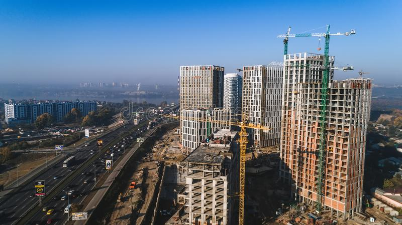Aerial view of landscape in the city with under construction buildings and industrial cranes. Construction site. Aerial view of landscape in the city with under royalty free stock image