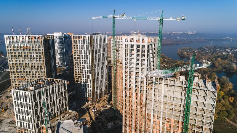 Aerial view of landscape in the city with under construction buildings and industrial cranes. Construction site. Aerial view of landscape in the city with under stock photos