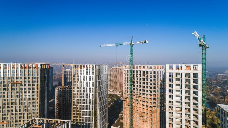 Aerial view of landscape in the city with under construction buildings and industrial cranes. Construction site. Aerial view of landscape in the city with under stock photo