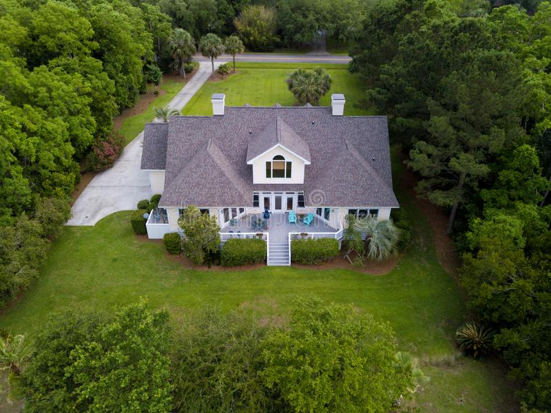 Aerial view of large home with on wooded grassy property. Aerial view of large home with new roof on wooded grassy property stock photos