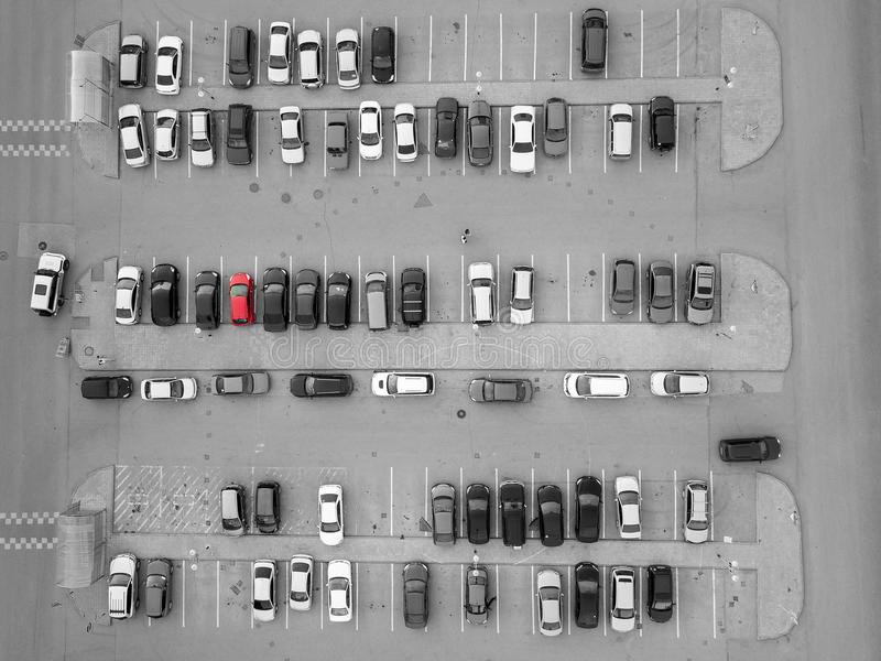 Aerial view of a large number of cars of different brands and colors standing in a parking. Aerial view of a large number of black-and-white and gray cars parked stock photo