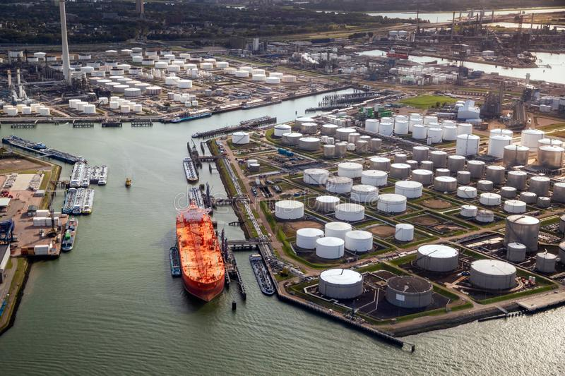 Aerial view of a large orange oil tanker moored at an oil storage silo terminal in an industrial port royalty free stock photography