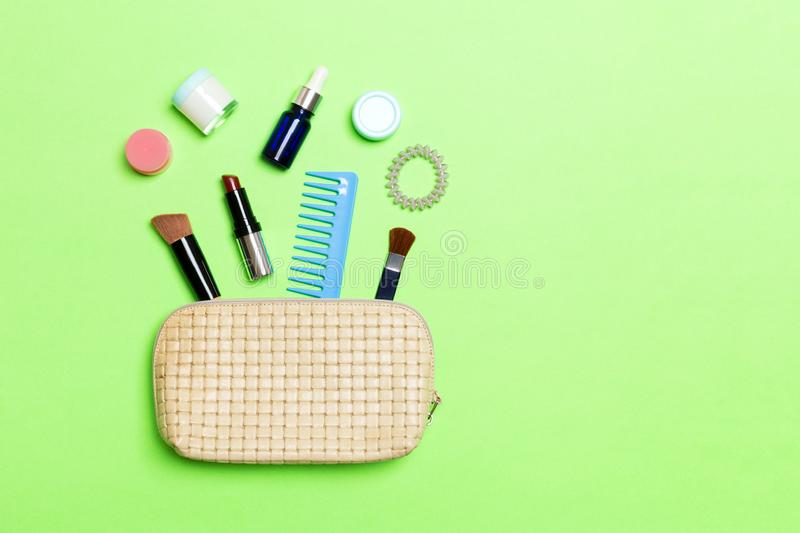 Aerial view of a leather cosmetics bag with make up beauty products spilling out on green background. Beautiful skin concept with. Copy space royalty free stock image