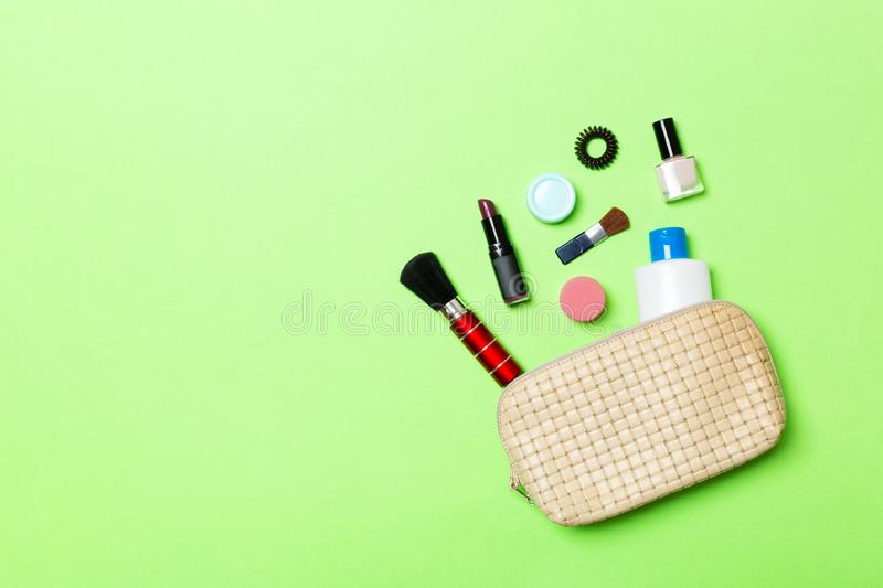 Aerial view of a leather cosmetics bag with make up beauty products spilling out on green background. Beautiful skin concept with. Copy space stock photos