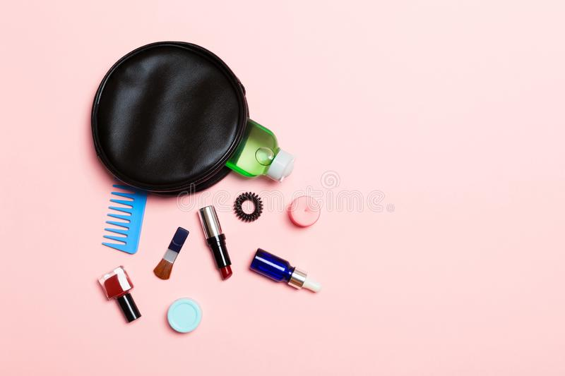 Aerial view of a leather cosmetics bag with make up beauty products spilling out on pink background. Beautiful skin concept with. Copy space royalty free stock photo