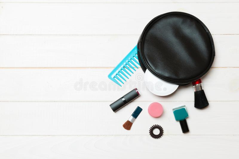Aerial view of a leather cosmetics bag with make up beauty products spilling out on wooden background. Beautiful skin concept with. Copy space stock photo