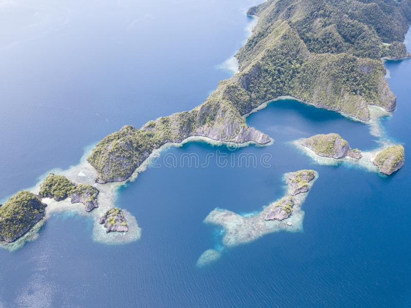 Aerial View of Limestone Islands and Reefs in Raja Ampat. The limestone islands found in Raja Ampat rise from calm, blue seas in a remote part of eastern royalty free stock photo