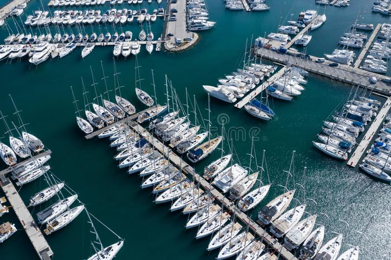 Aerial view of a lot of white boats and yachts moored in marina. Photo made by drone from above stock image
