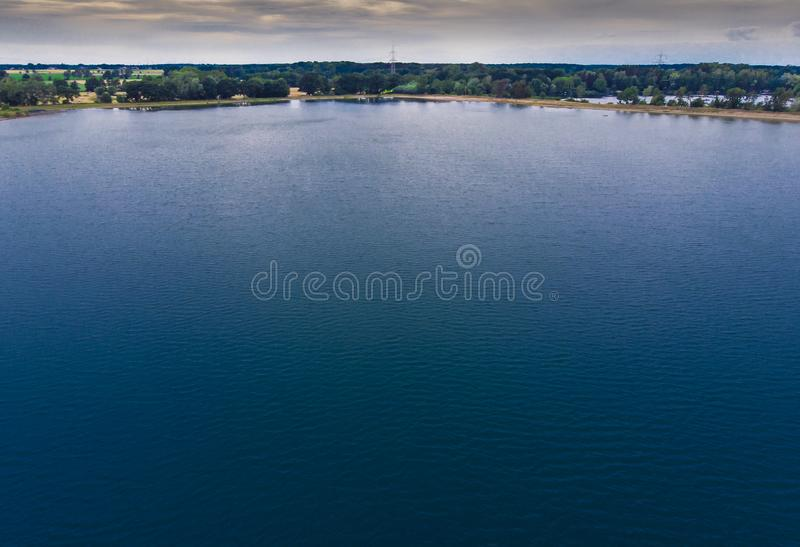 Aerial view from a low altitude of a dark lake with blue water and a strip of forest and a dramatic sky on the horizon. Made with drone royalty free stock photos