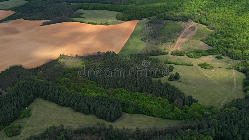 Aerial view of lowlands in western Slovakia, with fields, grassland, meadows and patches of light shining through clouds. stock photos