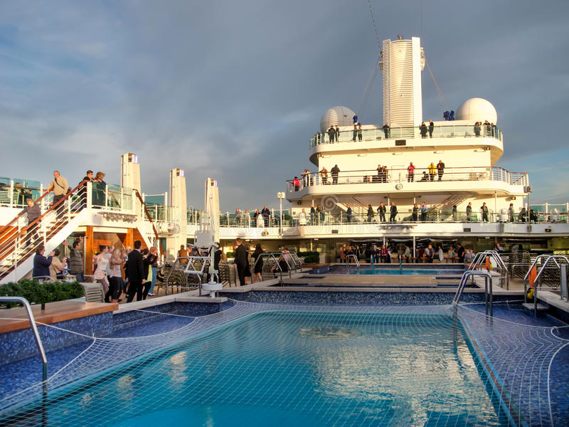 An aerial view of a luxury cruise ship pool area. An aerial view of a luxury cruise ship`s pool area on deck, during it`s twilight zone stock photo