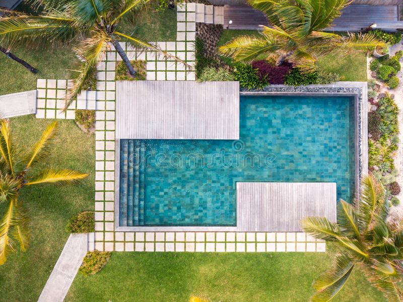 Aerial view of luxury hotel resort with swimming pool with stair and wooden deck surrounded by palm trees. royalty free stock photo