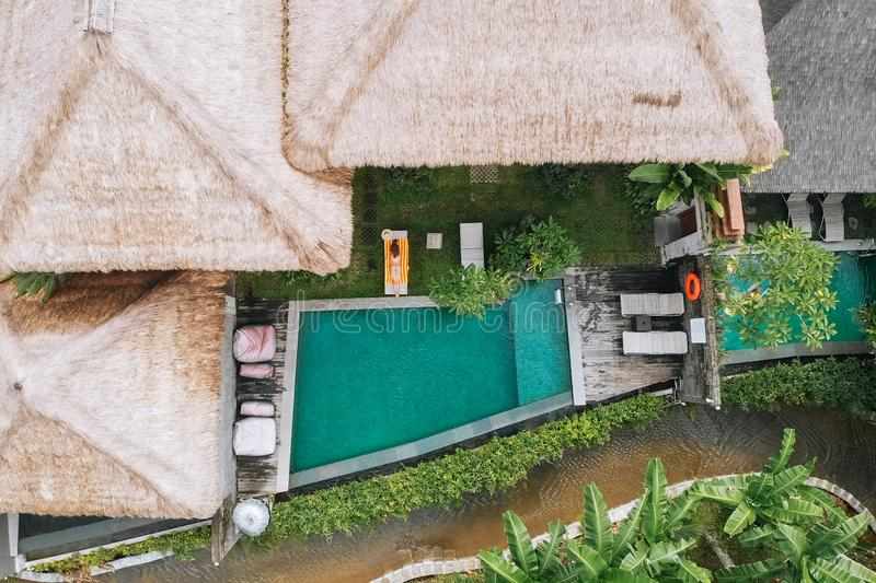 Aerial view of luxury hotel with straw roof villas and pools in tropical jungle and palm trees. Luxurious villa. Pavilion in forest, Ubud, Bali stock photos