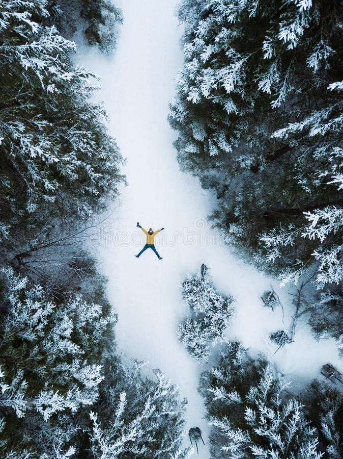 Aerial view of the lying man in winter forest stock photo