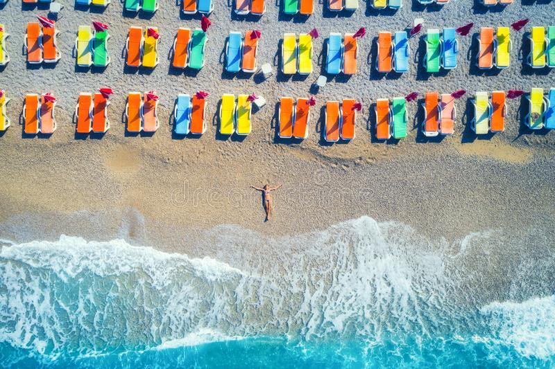 Aerial view of lying woman on the beach with colorful chaise-lounges. Beautiful young woman on the sea at sunset in Oludeniz royalty free stock photos