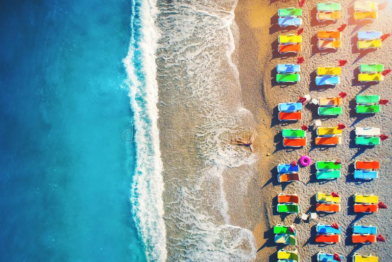 Aerial view of lying woman on the beach with colorful chaise-lounges royalty free stock photography