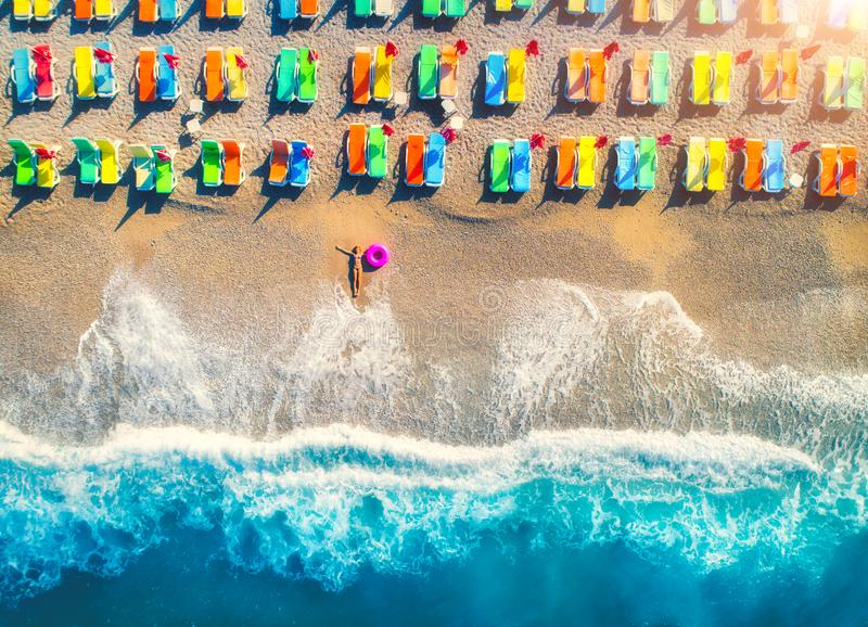 Aerial view of lying woman with swim ring in the sea. In Oludeniz, Turkey. Summer scene with young girl, blue water, waves and sandy beach with colorful chaise stock images