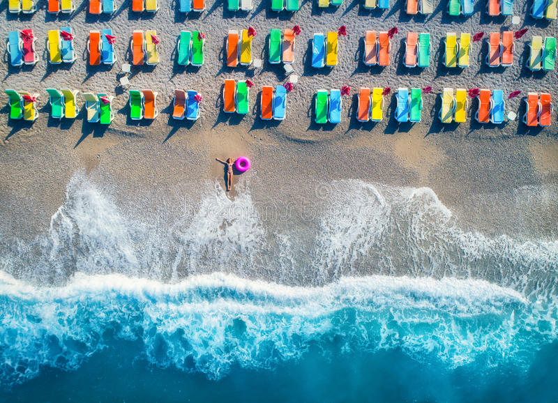Aerial view of lying woman with swim ring in the sea. In Oludeniz, Turkey. Summer seascape with girl, azure water, waves and sandy beach with colorful chaise
