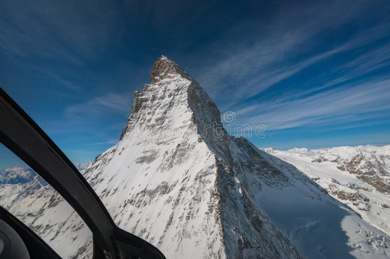 Aerial view of majestic Matterhorn mountain from inside a helicopter in front of a blue sky stock image