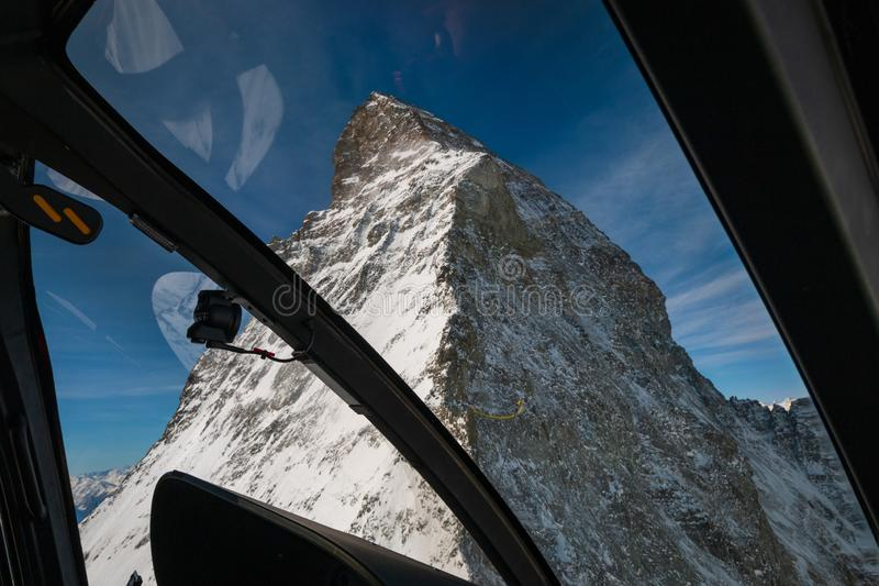 Aerial view of majestic Matterhorn mountain from inside a helicopter in front of a blue sky stock photos