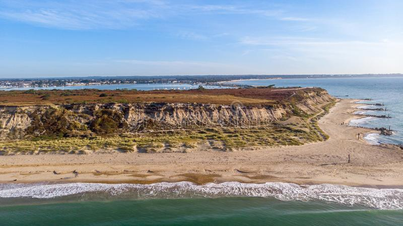 An aerial view of a majestic seacoast hill with huge cliff, sandy beach, groyne breakwater and crystal blue water under a royalty free stock photography