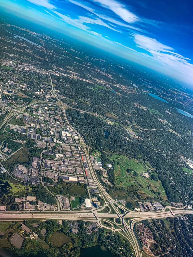 Aerial view of a major complex traffic interchange in a densely forested urban development. Aerial view of a major complex traffic interchange foreground in a royalty free stock photo