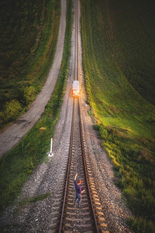 Aerial view A male hipster in a cap holding up a hand with a gesture Victory is standing on rails in front of an. Approaching train. Reverse vertical panorama royalty free stock image