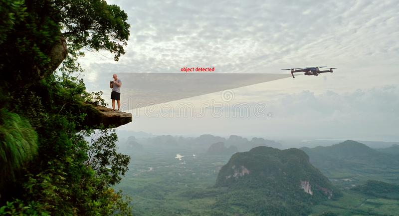 Aerial view of man drone operator on the mountain view point. Aerial view of man drone operator on the edge of the rock over beautiful green mountains and sky royalty free stock photography