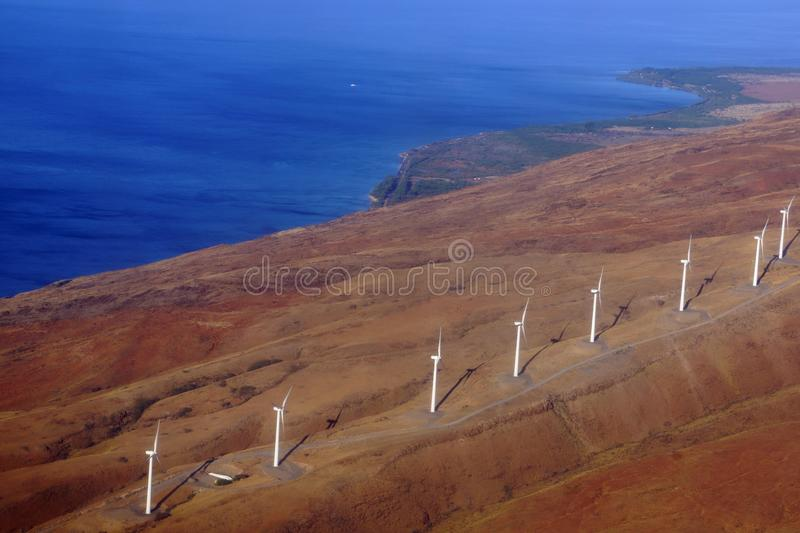 Aerial view of Modern Windmills spin on hillside. With windy road and coastline on the island of Maui stock photos