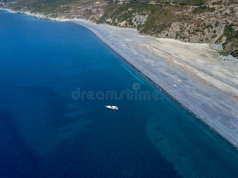 Aerial view of moored boat floating on a transparent sea. Nonza black beach. Corsica. France. Aerial view of a moored boat floating on a transparent sea. Diving stock images