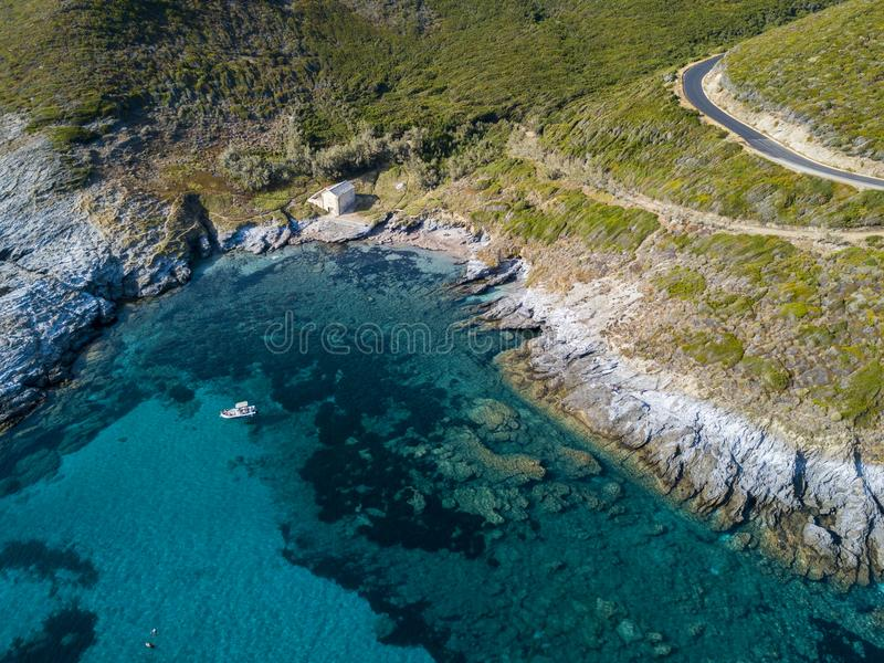 Aerial view of a moored boat floating on a transparent sea. Small house on the rocky coast of Cap Corse. Corsica. France stock photography