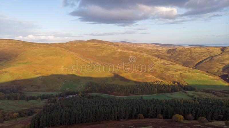 An aerial view of a mountain valley with grassy and stony slopes, trees and mountain range summits under a majestic blue sky and royalty free stock photo