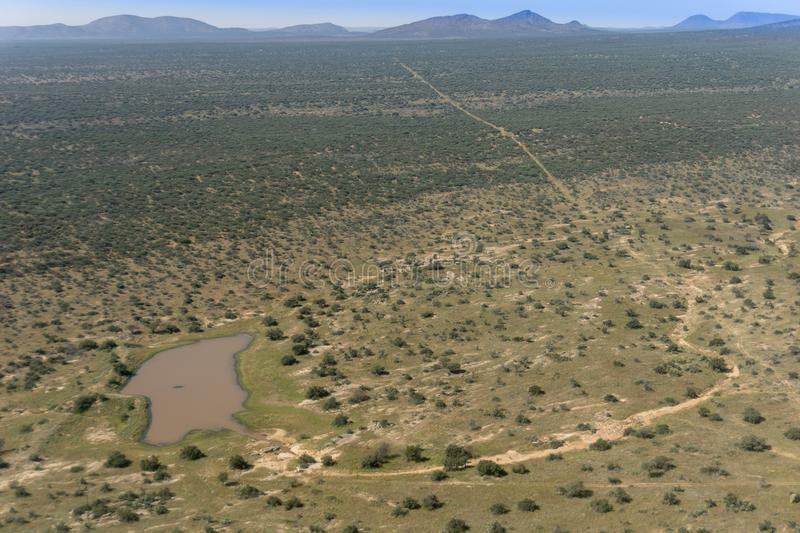 Aerial view Namibian landscape with waterhole,long roads and acacia tree bush scattered across land. royalty free stock photo