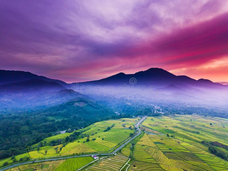 Aerial View natural beauty of the mountain with dense forests and green rice fields, morning sun with incredible sky i stock images