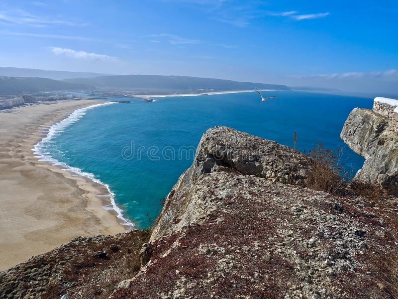 Aerial view of the long beach of Nazare in Portugal. Aerial view of Nazare at the Centro coast of Portugal with long beach and blue Atlantic ocean stock images